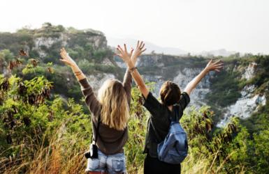 旅先で両手を広げる女性